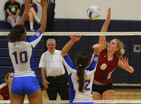 Madison's Margy Taylor makes a kill against Science Park's Briana Guzman and Patricia Bergamasco.